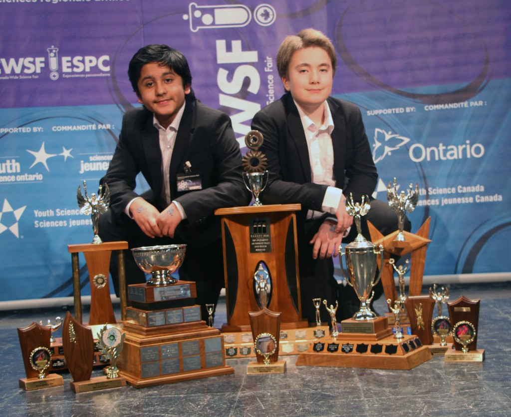 "(Pictured above: Aum Shah, left, and Vincent Jean-Louis, of Viscount Alexander Public School, pose with their hardware Saturday following the awards presentation at the United Counties Science Fair. Their project ""Solar Powered AA Battery Charger"" was a big winner at this year's fair.)"