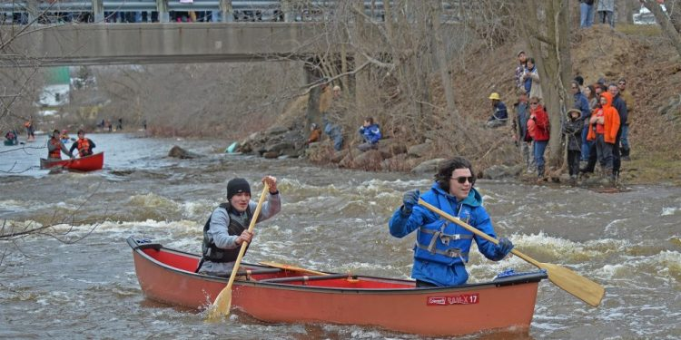 Spectators cheer on 350 paddlers from start to finish along 47th Annual Raisin River Canoe Race (photo credit : Rob Fry).