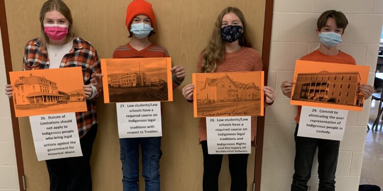 Students from Smiths Falls District Collegiate Institute hold pictures of residential schools with attributed Truth and Reconciliation Calls to Action Recommendations.