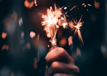 person holding a sparkler in macro photography