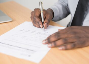 person holding gray twist pen and white printer paper on brown wooden table
