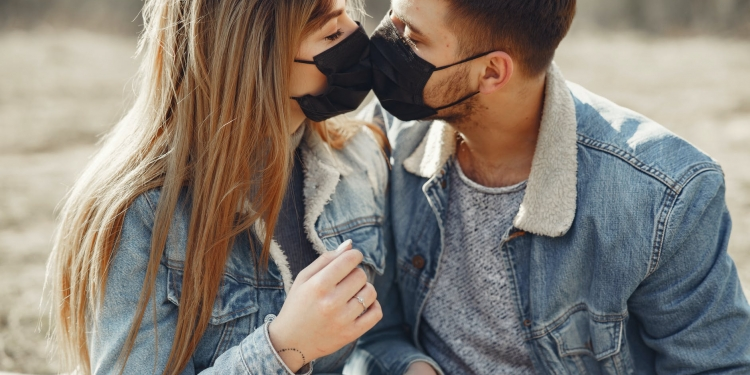 loving young couple kissing while wearing black medical masks