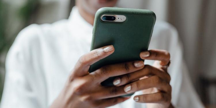 black woman messaging on modern cellphone