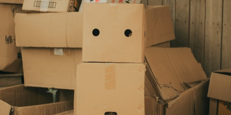 anonymous person with box on head near carton boxes