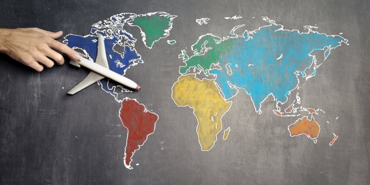 person with toy airplane on world map