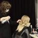 hairdresser making hairdo for client in dressing room