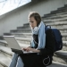 woman sitting on concrete stairs using laptop