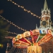 colorful luminous carousel against kremlin on red square at night