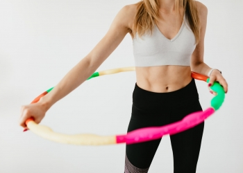 crop sportswoman exercising with gymnastic hula hoop