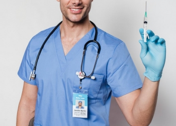 cheerful tattooed doctor with syringe in uniform