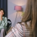 happy young woman smiling while talking to psychologist in modern office