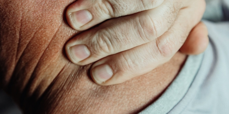 close up photo of a person having a neck pain
