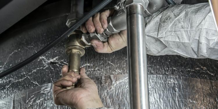 plumber installs pipe fittings