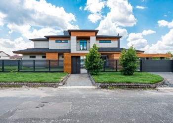 exterior of fenced modern villa in suburb area