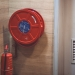 red fire extinguisher below hose reel
