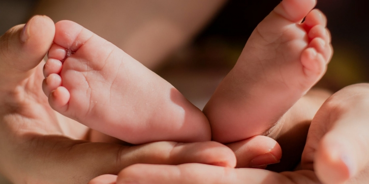 person holding babys feet
