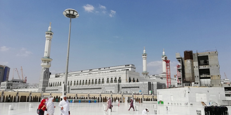 unrecognizable muslim pilgrims near ancient mosque on sunny day